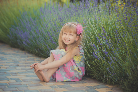 Blond young baby girl have some fun during summer vacation holidays posing fashion style session close to green spring lavander. Stock Photo