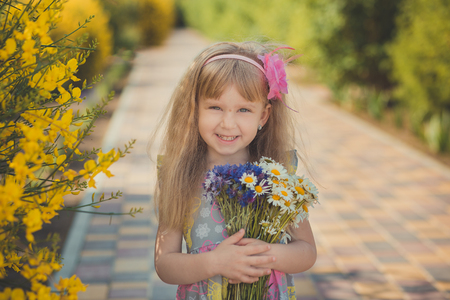 Blond young baby girl have some fun during summer vacation holidays posing fashion style session close to green spring wild yellow flowers.