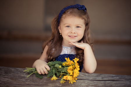 Young baby girl with brunette hairs and bright perfect skin cheeks wearing stylish awesome blue dress posing with bouquet of wild yellow flowers daisy. Stock Photo