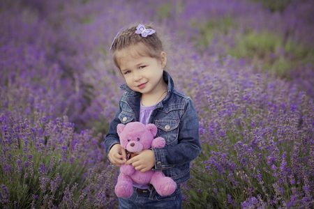 Adoreable cute blond Young beauty girl in blue jeans and purple shirt with Teddy bear in hands posing to camera with cosy smile face on lavender field lea park