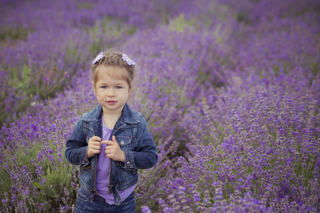 Beautifull cute blond Young beauty girl in blue jeans and purple shirt posing to camera with cosy smile face.Wellbeing time spending in village fields of lavender in august France Provence.