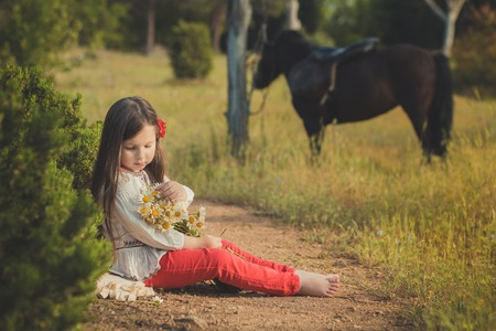 Girl with brunette hair and brown eyes stylish dressed wearing rustic village clothes white shirt and red pants on belt posing with black young horse pony.