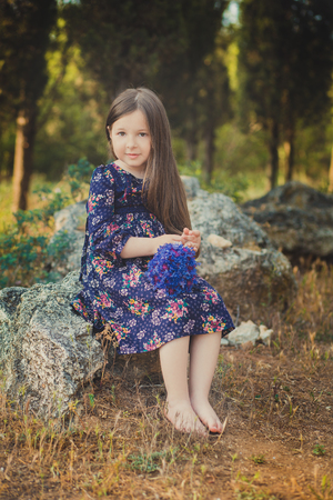 Cute baby girl with brunette hair and brown eyes portrait with deep blue purple wild flowers barefoot wearing stylish colorful flower dress and looking to camera with shining face.