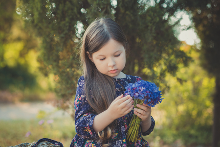 Cute baby girl with brunette hair and brown eyes portrait with deep blue purple wild flowers barefoot wearing stylish colorful flower dress and looking to camera with shining face. 免版税图像
