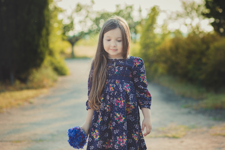 Cute baby girl with brunette hair and brown eyes portrait with deep blue purple wild flowers barefoot wearing stylish colorful flower dress and looking to camera with shining face. Фото со стока