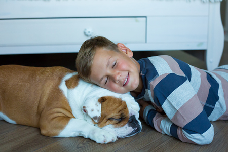 Handsome Young Boy kid wearing cozy pajamas Playing with His english funny bull Dog on the floor and enjoy life time weekend hanging each other with love and tender.