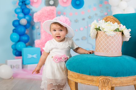 Cute little baby girl with big blue eyes wearing tutu hat and flower in her hair posing sitting in studio decorations with number one celebrating her birthday. Banco de Imagens