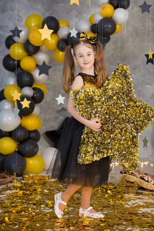 Movie super star girl model posing in studio shoot with golden star and colorful baloons wearing stylish gold airy dress with shining bow tie.Super star pillow deisigned by photographer Stockfoto