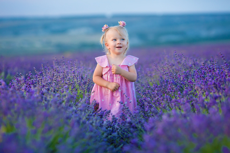 Cute little girl in airy pink dress posing standing on a lavender field and looking to clouds.