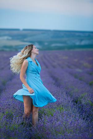 Sex appeal blond woman in airy blue dress enjoy life time vacation on fresh lavender field by walking or spinning around. Sylph attractive lady dancing on flowers