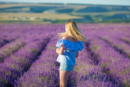 Smiling beautiful blond lady model on lavender field enjoy summer day wearing airy whit dress with bouquet of flowers Stock fotó