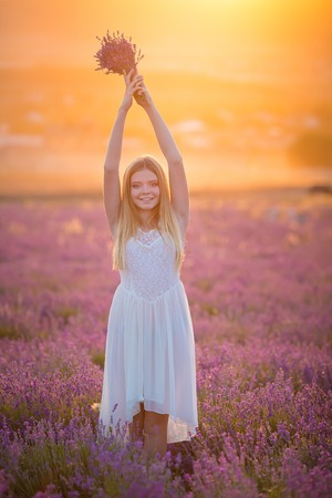 Smiling beautiful blond lady model on lavender field enjoy summer day wearing airy whit dress with bouquet of flowers Imagens