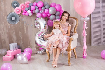 Mother with daughter celebrating family event both dressed in pink airy fancy dresses wearing golden crown on head.Studio shoot of lovely family with soft tender pastel colors 免版税图像