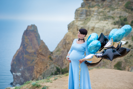 Pregnant woman posing on mountain coast line wearing blue long dress with air baloons Stok Fotoğraf