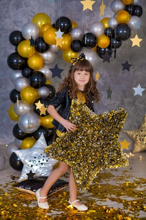 Cute party girl in golden dress posing in club studio with golden stars and air baloons. Pillow stars SUPER STAR designed by photographer