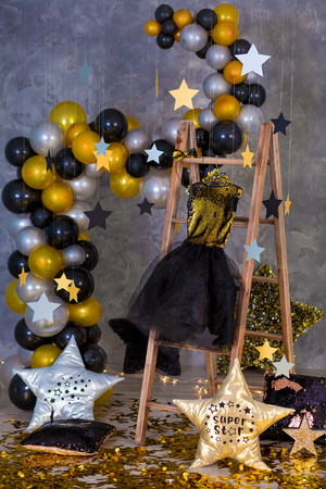 Decoration of golden party dress with leather jacket hanging on wooden hanger in club studio decorations Stock Photo