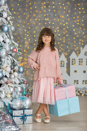 A child in the studio for the New Year. Girl in a Christmas photo session. Festive mood. Waiting for a miracle in the Birth. Фото со стока