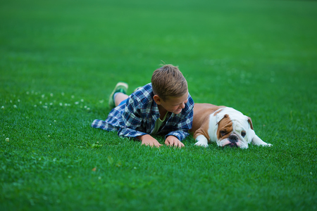 Little boy teenager with his dog bulldog in park on a sunny day on green grass park land enjoy life together with his friend.