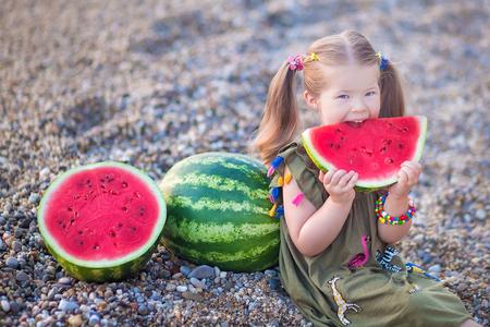 Girl eating watermelon on the beach, summertime enjoying beautiful day close to ocean. 写真素材