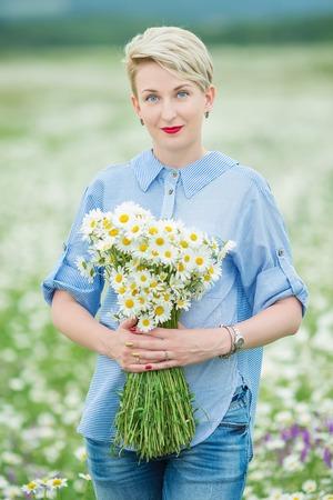 Beautiful young woman enjoying freedom on flower field Stock Photo