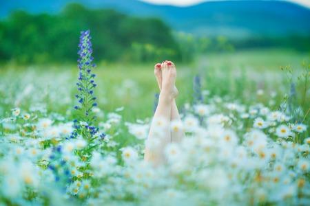 Entspannung in der Natur Frau Beine zwischen Blumen Spa.
