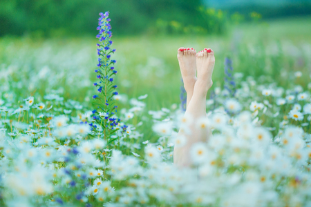 relaxing in the nature Woman legs between flowers spa. Stock Photo