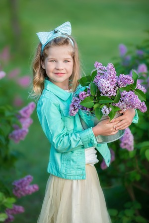 Cute girl in blue jackets with fairy airy skirt standing close to lilac bush.