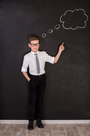 Handsome school boy in goggles white shirt tie standing close to school desk with thinking cloud above the head