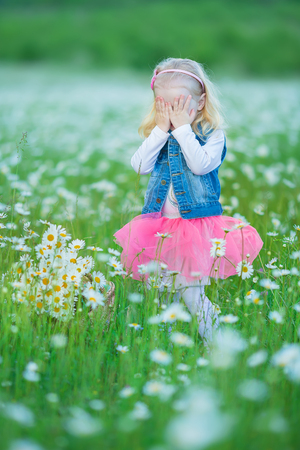Cute little smiling baby girl in chamomile field. Little blond child with wreath on head in chamomiles wearing jeans and pink skirt enjoying hide-and-seek, whoop, peek a boo.