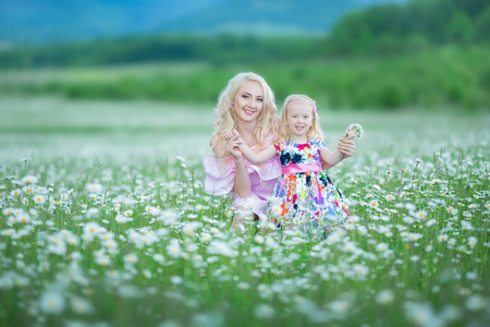 Blond mother with cute little daughter wearing white colourful pink dresses in chamomile field, summer time. Enjoying spending time together happy childhood.