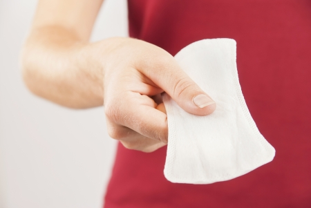 Young woman wearing red t-shirt holding menstrual pad Stock Photo