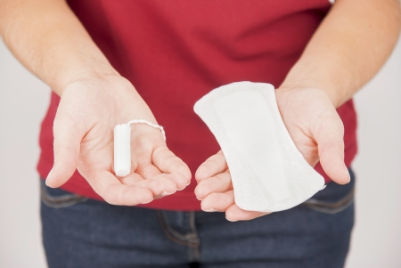 Young woman choosing between pad and tampon