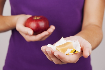 quandary: Young woman preferring fruit instead of candy