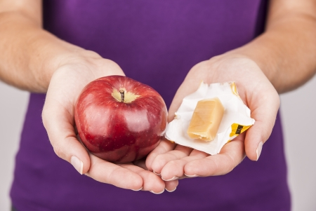 Young choosing between healthy fruit and candy Stock Photo