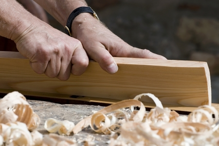Wood work: Close-up of carpenter s hands with bench plane at work