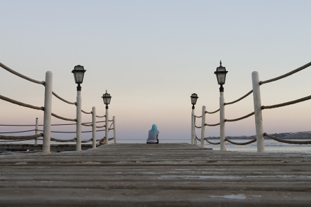 Arabic woman sitting alone on a jetty photo
