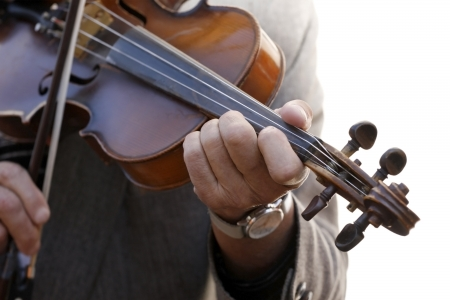 Close-up view of hands playing the violin