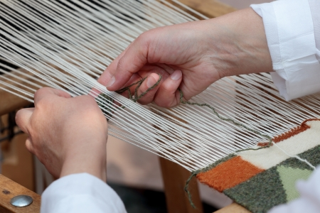 Close-up view of hand loom weaver's hands at work Standard-Bild