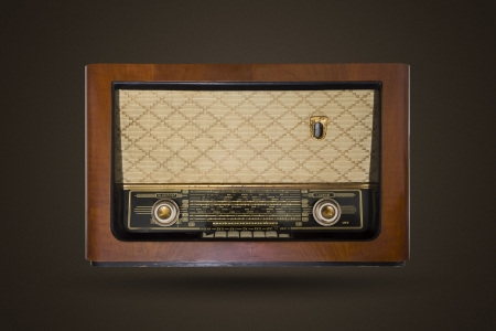 Picture of an old vintage, wooden radio isolated on brown background with noise.