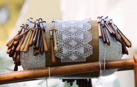 Traditional equipment for lace making - wooden bobbins on lace pillow with pricked paper pattern
