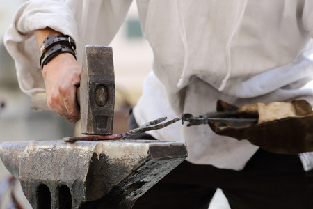 Hands of a blacksmith at work with typical tools  Standard-Bild