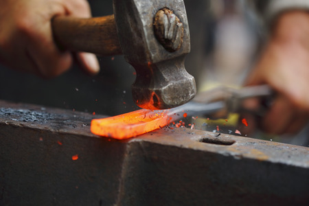 Detail shot of hammer forging hot iron at anvil