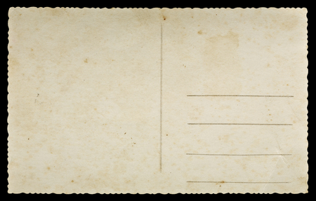 Old paper postcard with decorative fluted edges isolated on black background
