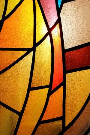 Nahaufnahme eines bunten Buntglasfensters, das von der Sonne beleuchtet wird