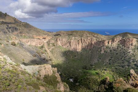 View of the mountainous landscape of volcanic origin along with lots of trees and vegetation and on the horizon, you can see the setting moon Gran Canary island