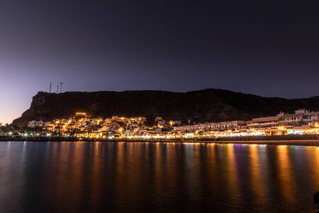 Mogan beach during sunset with the city lit up by street lights and freshly lit streets of the grand canary island valley