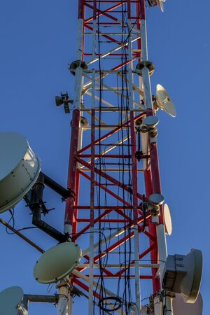 Closeup of a broadcast tower full of devices with a blue sky in the background. Banque d'images