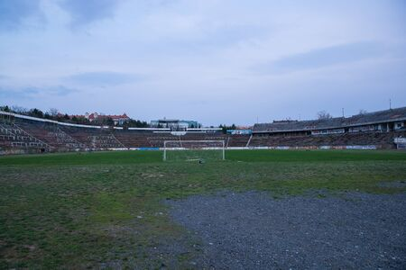 Abadoned Stadion Za Lužánkami is a currently inactive stadium in Brno, Czech Republic. Captured in spring sunset, sky and clouds was colored to blue dark colors. Photo from tribunes and inside middle of field. Stock Photo