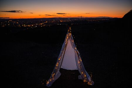 Teepee during dark sunset in quarry Hady Brno with view on city centre. Stock Photo