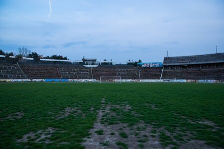 Abadoned Stadion Za Lužánkami is a currently inactive stadium in Brno, Czech Republic. Captured in spring sunset, sky and clouds was colored to blue dark colors. Photo from tribunes and inside middle of field.